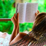 Mujer en una tumbona en su jardín leyendo un libro sobre paisajismo y arquitectura del paisaje
